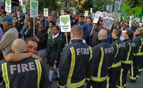 A demonstrator hugs a firefighter at a Grenfell vigil