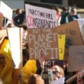 """placard says """"planet over profit"""""""