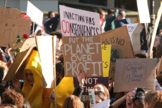 "placard says ""planet over profit"""